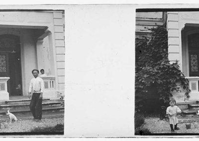 Homme, enfant et chien devant une maison, s.d.