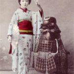 Une femme en kimono posant près d'une armure de Samouraï